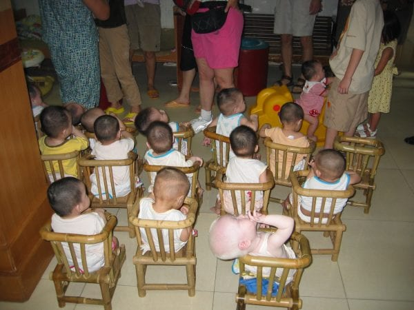 Babies lined up in their wooden chairs at the orphanage