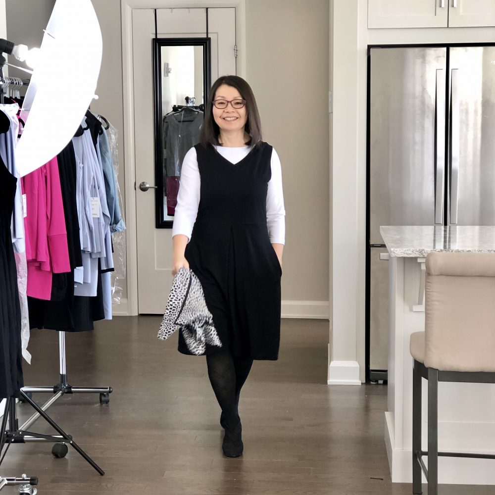 Colleen is wearing the Midnight Black Carolyn reversible dress with the V-neck in front over a white 3/4 sleeve t-shirt and black tights and heels. She has a black & white silk scarf in her hand.