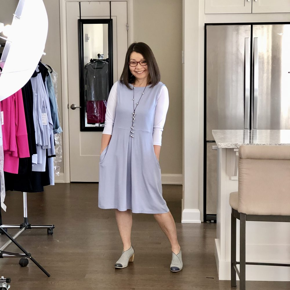 Colleen is wearing the Silky Blue Carolyn reversible bamboo dress over a white 3/4 sleeve t-shirt. She has her hands in the pockets. She's accessorized with a pearl rope necklace and funky blue shoes.
