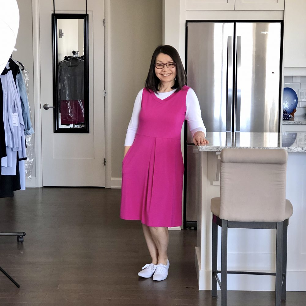 Colleen is wearing the Fiery Fuchsia Carolyn reversible bamboo dress over top a white 3/4 sleeve t-shirt, and she has on white Keds.