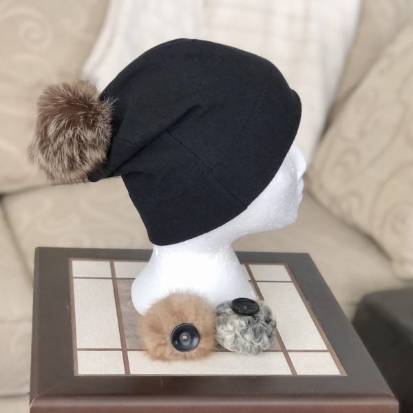 Black bamboo toque on a mannequin head with a large detachable racoon pompom and a medium beige mink pompom and a small grey Persian lamb pompom with black buttons sewn on the bottom lying in front