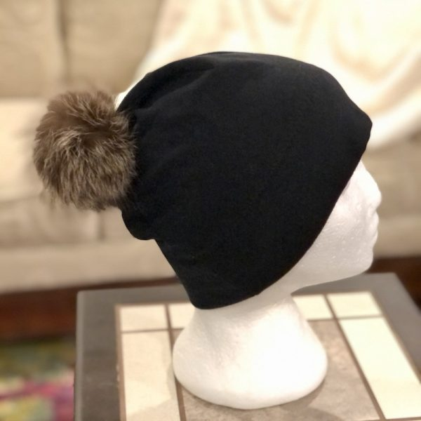 Black bamboo toque with a large raccoon pompom on a mannequin head