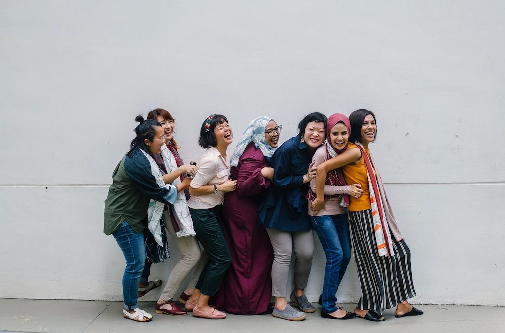 How can we as women support one another? by Colleen Kanna, Photo of 7 culturally diverse women laughing and holding on to one another taken by MentatdgtfromPexels