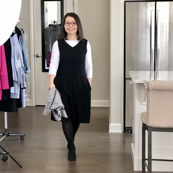 Transitional dressing while the weather sorts itself out. Colleen is wearing the Midnight Black Carolyn reversible dress with the V-neck in front over a white 3/4 sleeve t-shirt and black tights and heels. She has a black & white silk scarf in her hand.