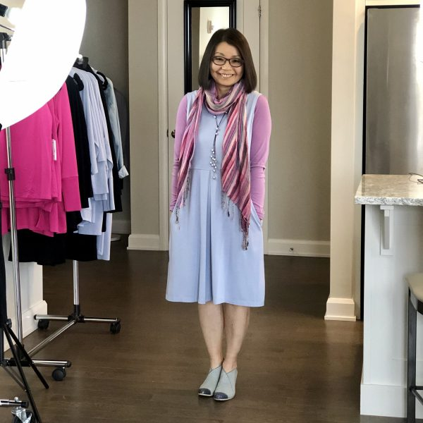Transitional dressing while the weather sorts itself out. Colleen is wearing the Silky Blue Carolyn reversible bamboo dress with pockets over a mauve long-sleeved top with pearl rope necklace and funky blue heels.