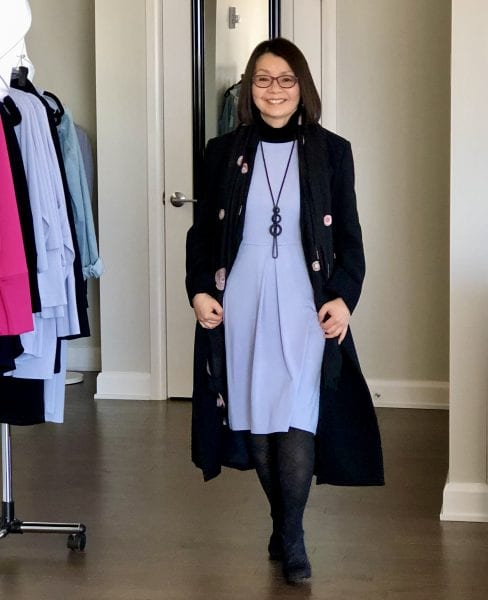 Colleen in the silky blue Carolyn with black pendant necklace, tights & shoes, and overtop a full length black coat and scarf.