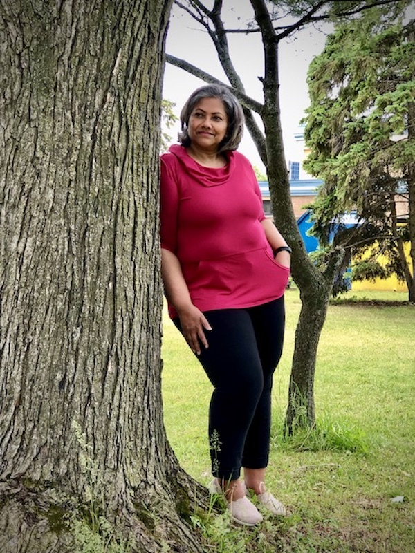 Pamela George in the raspberry Pamela bamboo hoodie leaning against a tree